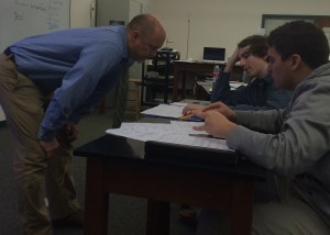 Mr. Williamson helps his students on their physics assignment. Photo credit: Morgan Baxter