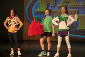 "Woody, Andy, and Buzz from ""Toy Story"" proudly carry the senior girls' presents"