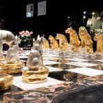 Leão reina em tabuleiro de jogo de xadrez com gatos selvagens