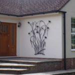 Painel de ferro forjado com flores e pássaros na fachada de casa