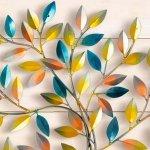 Árvore com folhas coloridas de tons degradê em painel de metal