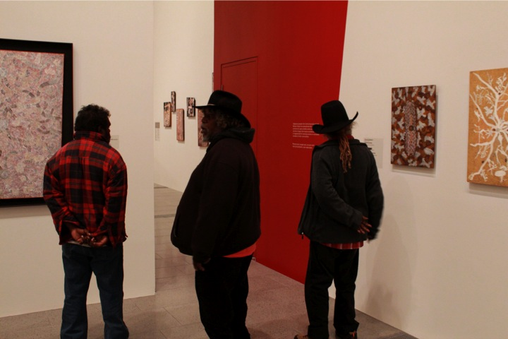 "Fig. 4. Three Pintupi men standing at the entrance to the room of restricted paintings at the ""Tjukurrtjanu"" exhibition at the National Gallery of Victoria in Melbourne, October 2011. Photographer unknown (Fred Myers)."