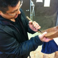Alex McCarty of the Makah demonstrating carving techniques on a miniature canoe, Author's Photo. Evergreen State College, 2015