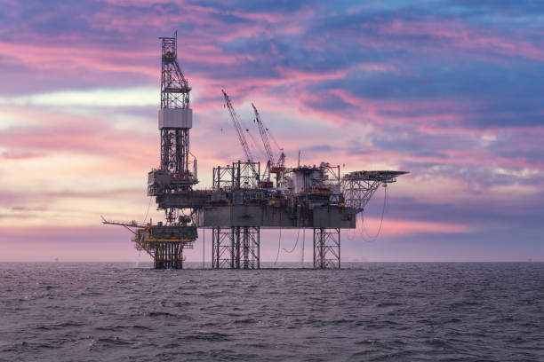 Drilling rig with oil and gas platform is working at offshore for producing crude oil, natural gas and produced water in petroleum industry that shows the steel construction of heavy platform and drilling rig under the colorful sky at the sunset time.