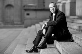 Black and white photo of a suited and booted man sat laughing on the Bank of England's steps