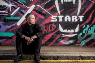 """Man with ponytail sitting on pavement with graffiti wall behind, with the word """"start"""" in the jaws of a lion"""