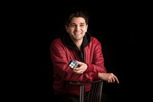 Maddox Magic sitting on a chair, black backdrop with Rubik's Cube