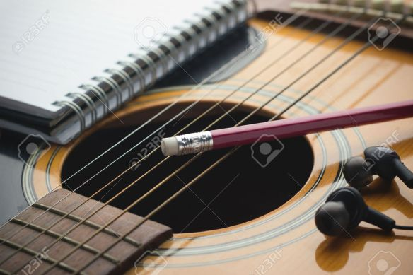 31035991-notebook-and-pencil-on-guitar-writing-music-stock-photo