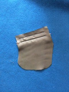 "This shows the lining material for one side of the pocket bag sewn to the ""right side"" of the coat along the top and bottom only. Hidden beneath it is the welt, sewn along the bottom only and upside down."