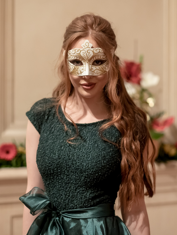 Portrait of a redheaded model in a green evening dress and a classical mask at the Hofburg in Vienna.