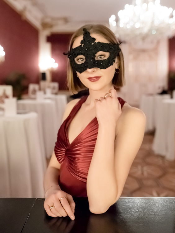 Portrait of a redheaded model in a red evening dress and a classical mask at the Hofburg in Vienna.