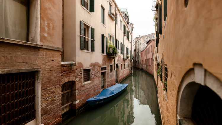 Blue gondola in a narrow channel in Venice with the buildings reflecting in the water
