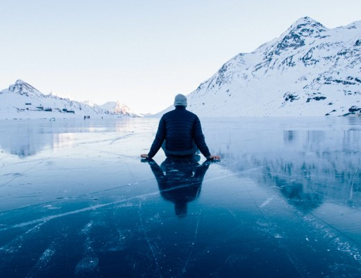 self-doubt man sitting on ice with mountains in distance