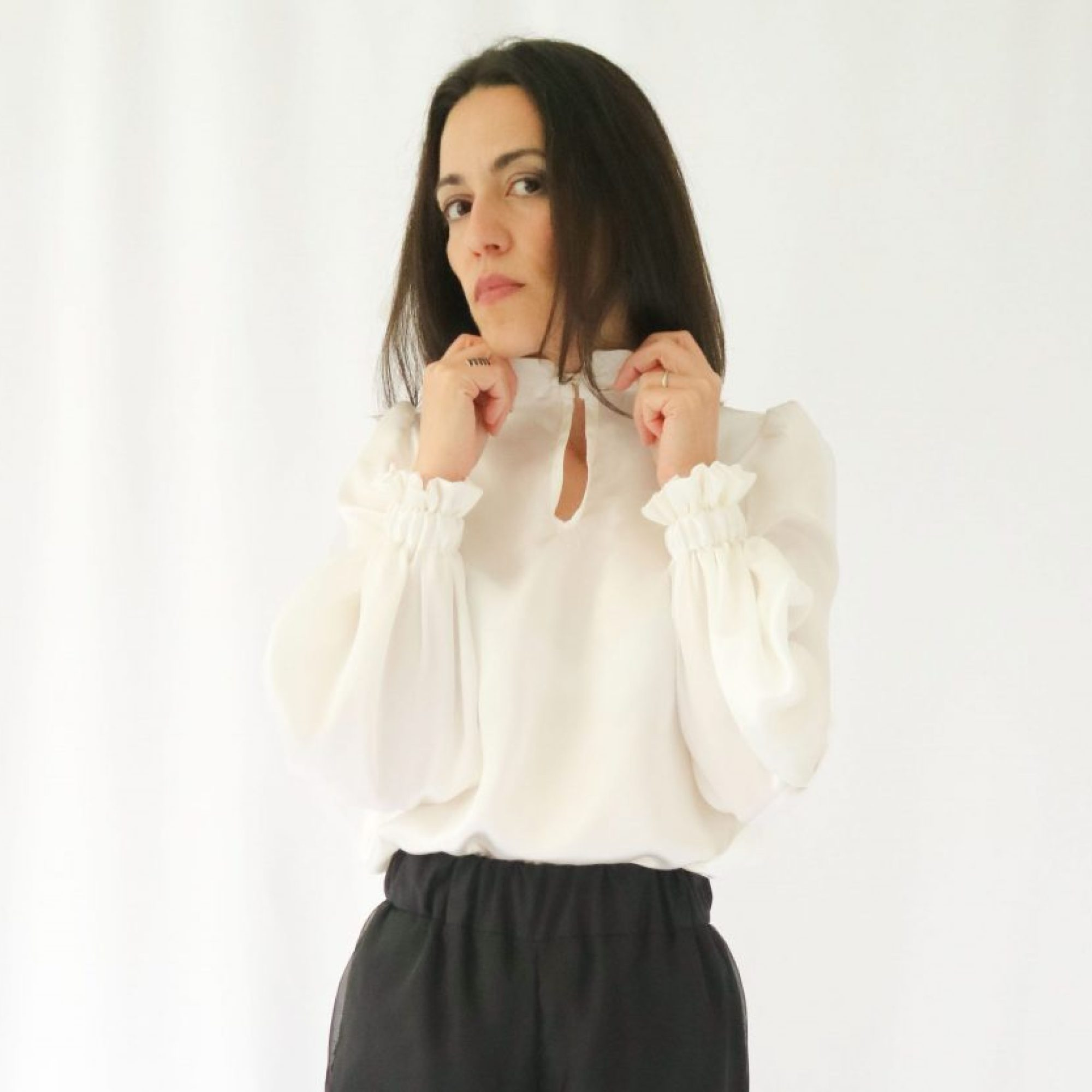 A woman wearing a white pearl silk blouse. and black trousers. The woman has both hands adjusting the blouse's collar.