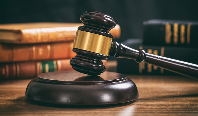 Judge gavel on a wooden desk, law books background. is cbd oil legal in hawaii? buy hemp-derived CBD products in hawaii.