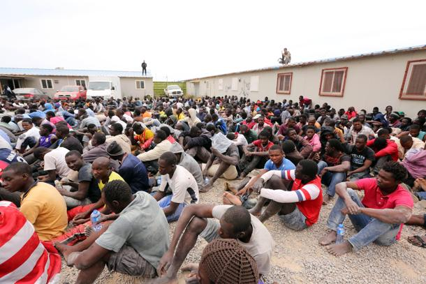 Migrants from sub-Saharan Africa rest inside a detention center in the Libyan capital Tripoli on June 4, 2015. Authorities, acting on a tip off, stormed a hideout where more than 500 illegal migrants, mostly men from African, were waiting for people smugglers to take them to boats to Europe, migration officials in Tripoli said. AFP PHOTO / MAHMUD TURKIA