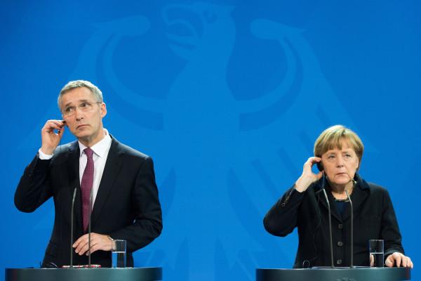 Stoltenberg e Merkel. L'auricolare manda un suono confuso.