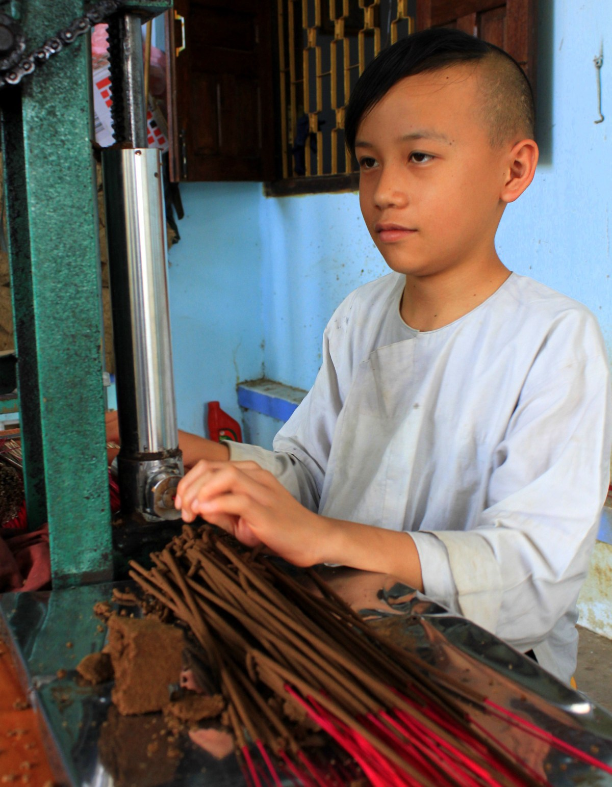 A little boy making incense in Central Vietnam