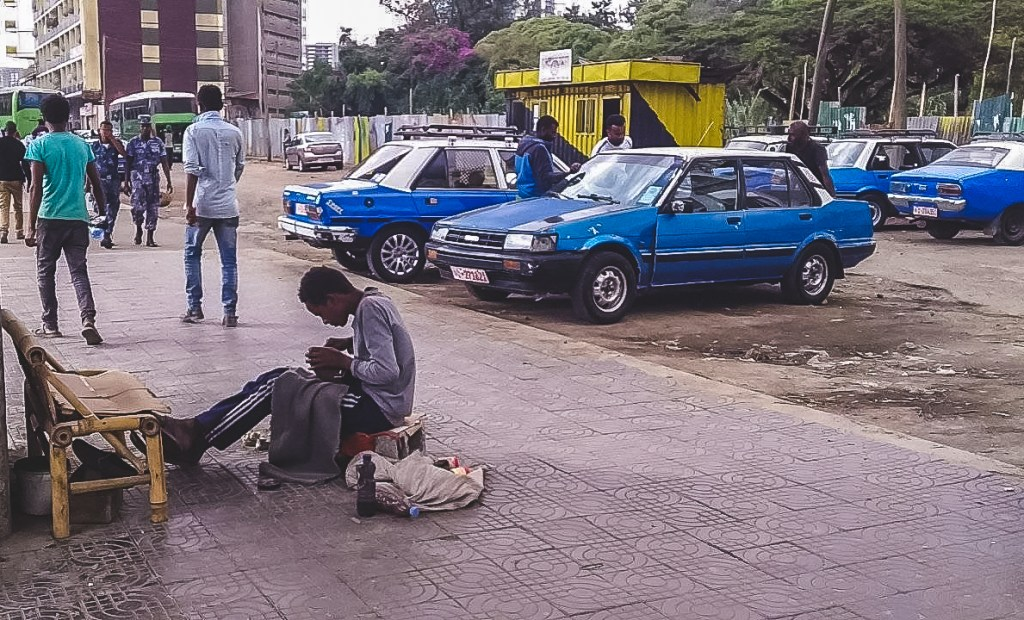 A street of Addis Ababa in Ethiopia with its blue cars and shoe shiners.
