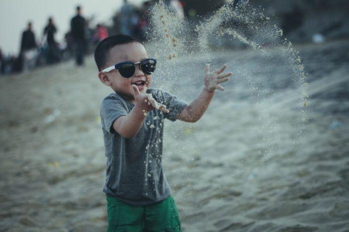 Niño jugando alegre con la arena de la playa con una conducta positiva