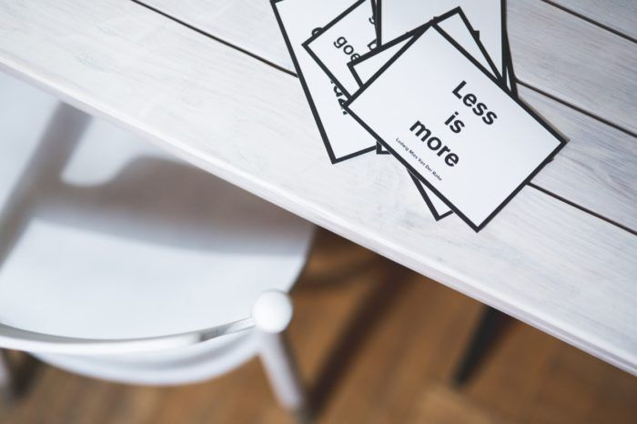 """Escritorio minimalista con la cita """"menos es más"""" en una tarjeta de visita"""