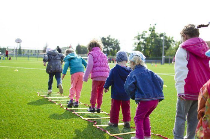 Niños y niñas desarrollando la psicomotricicdad gruesa a través de ejercicios al aire libre