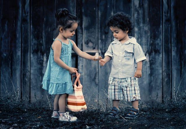 Dos niños cogiendo una flor en la naturaleza