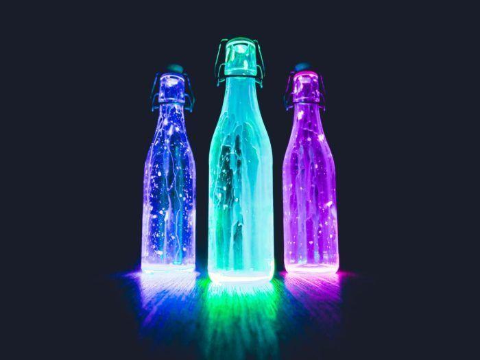 Mesa de luz con botellas iluminadas