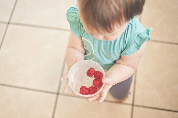 Niña llevando fresas demostrando por qué los niños no comen