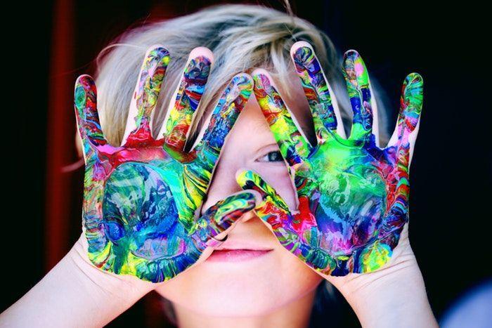 Niño con las manos pintadas como en la pedagogía Reggio Emilia