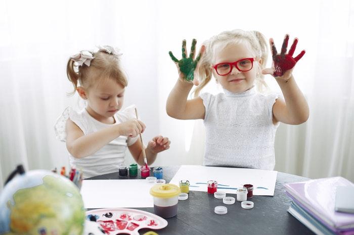 Dos niñas pintando como una de la rutinas en la escuela infantil