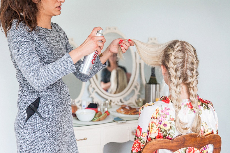 Bride getting her hair plaited on her wedding day