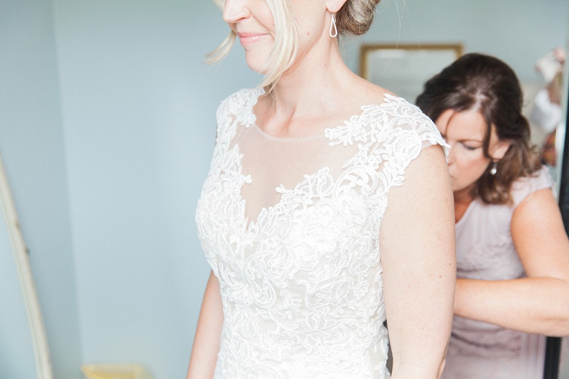 Bride getting into her Maggie Sottero dress with her mother