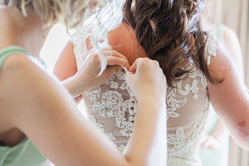Bridesmaid Doing Up Brides Dress at Lake Eland Game Reserve