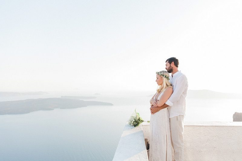 Newlywed Couple Looking Out At The View Of The Caldera In Santorini