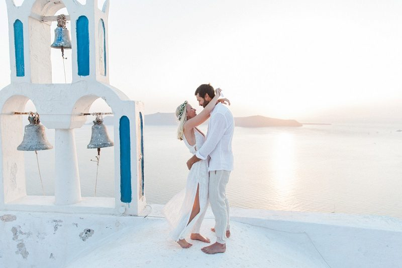 Bride and Groom on a Church Roof After Their Sunset Elopement in Santorini