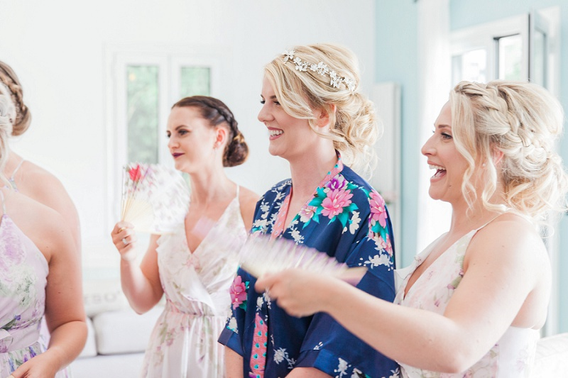 Smiling bride being fanned by her bridesmaids before she gets into her dress