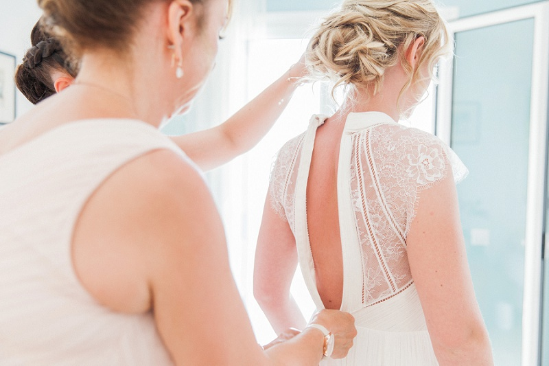 Bride being zipped into her Catherine Deane dress by her mother