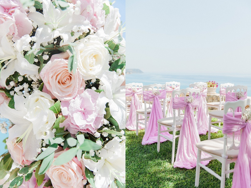 Close up of the pink and white floral arch and decorated white chairs with a view of the Ionian Sea.