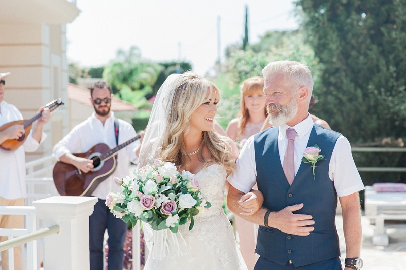 Bride smiling at her father in the sunshine before they walk down the aisle together.