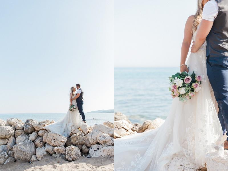 Bride and groom embrace on the rocks on a Kefalonian beach