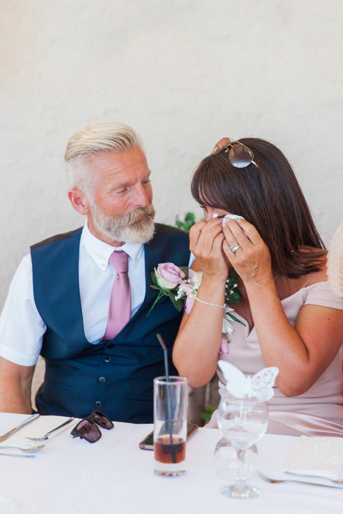Mother of the bride being comforted by her father after tearing  up during his speech