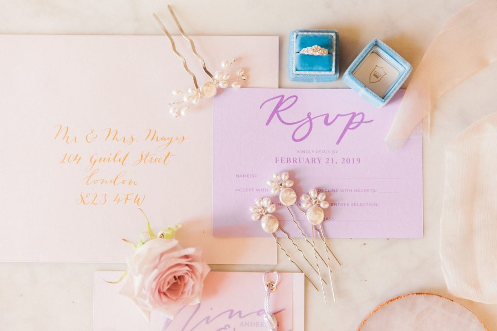 Pastel flatlay featuring wedding stationery by Scritto and accessories by PS With Love