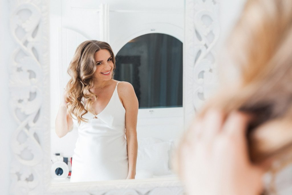 Bride smiles as she does her hair ahead of her elopement at Dana Villas Santorini