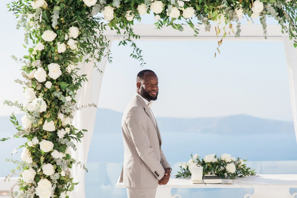 Grooms smiles as his bride arrives at their elopement ceremony in Santorini