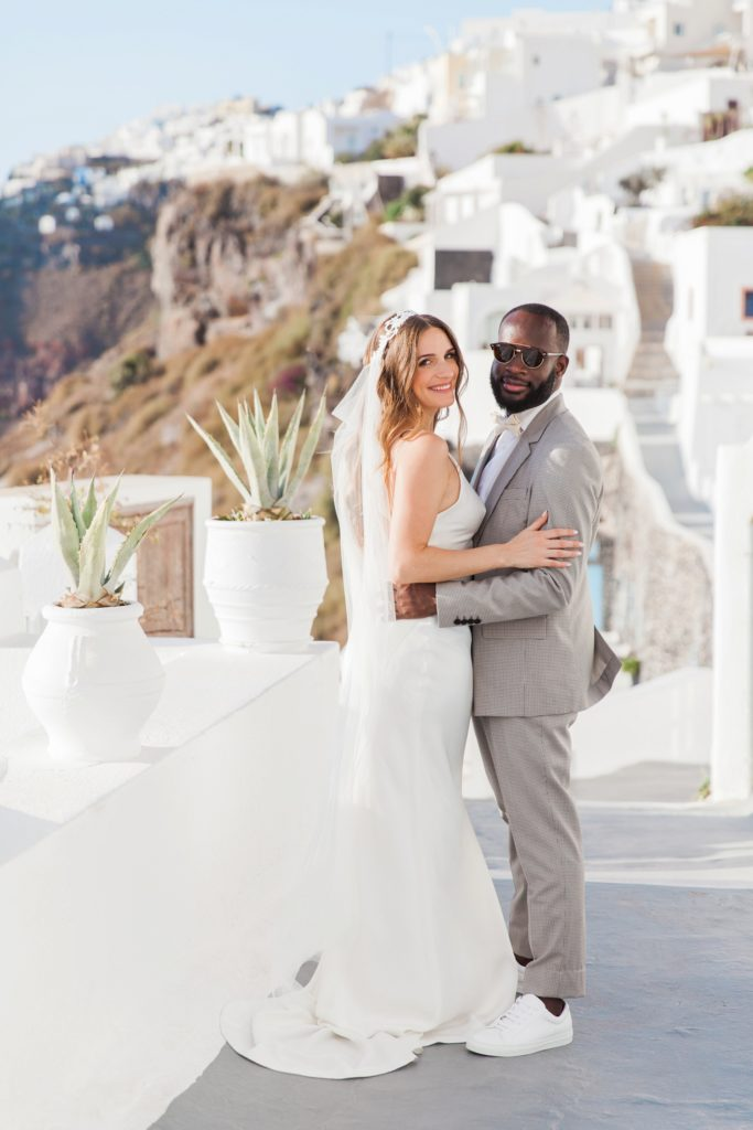 Bride and groom smile on the streets of Santorini after their elopement