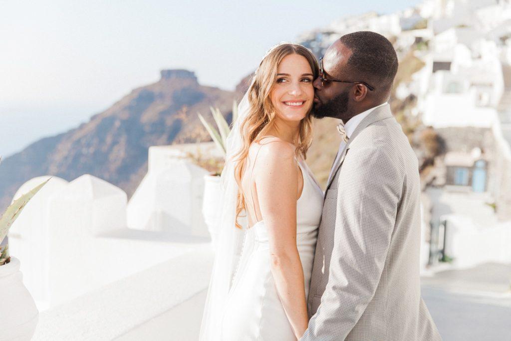 Groom kisses the bride against a view of Skaros Rock in Santorini