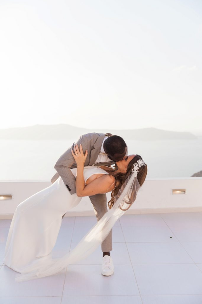 Groom kisses his bride as he dips her during their first dance at their Santorini elopement