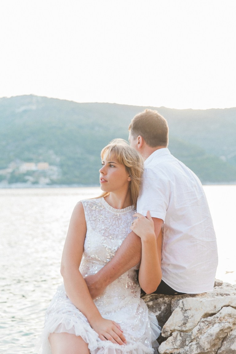 Couple sitting on the rocks over looking the sea during their sunset honeymoon photography session in Lefkada
