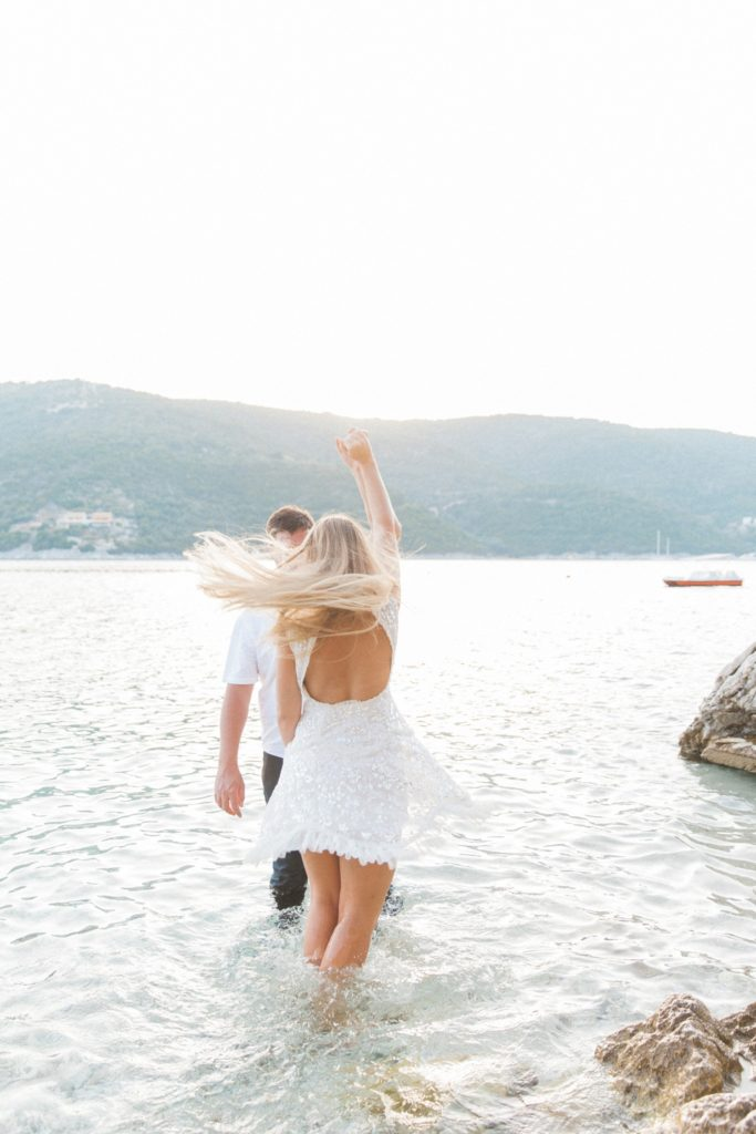 Couple dancing in the sea during their honeymoon photography session on Lefkada